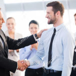 stock-photo-good-job-two-cheerful-business-men-shaking-hands-while-their-colleagues-applauding-and-smiling-in